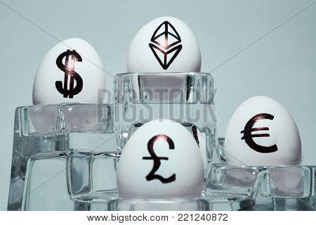 The inscription on chicken eggs for advertising and promotion of various currencies and crypto. Written or drawn symbols British pound sterling. dollar. Euro. Ethereum.