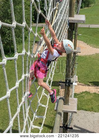 Daring young girl climbing on an elevated rope net on an obstacle course.  Reaching for a handhold, expressing courage and determination.
