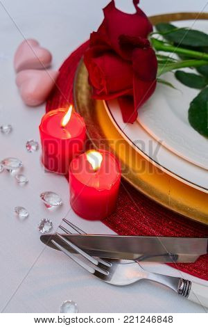 Valentines Day Dinner - plate with flowers, burning candles and cutlery