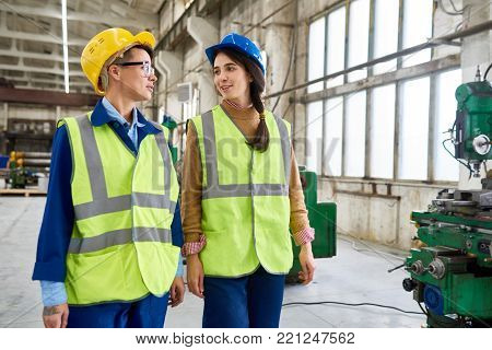 Portrait of two modern young women working at factory talking to each other while crossing big workshop, copy space