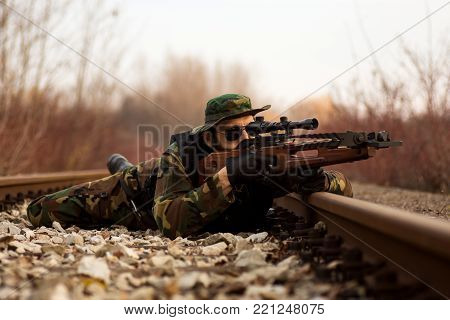 The military man is lying down on railway and aiming with crossbow weapon to target outdoors.