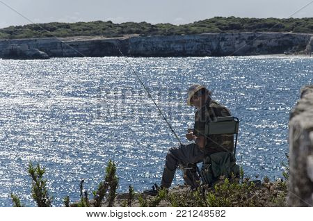 Torre dell'Orso, Italy - September 22, 2017: Solitary fisherman engaged in bait preparation