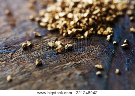 a mound of gold nuggets on a grungy rough wood work table.