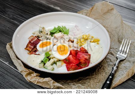 Top View Healthy Hearty Cobb Salad with Chicken, Bacon, Tomato, Onions, Eggs, green beans. American food. Close up, home made cuisine