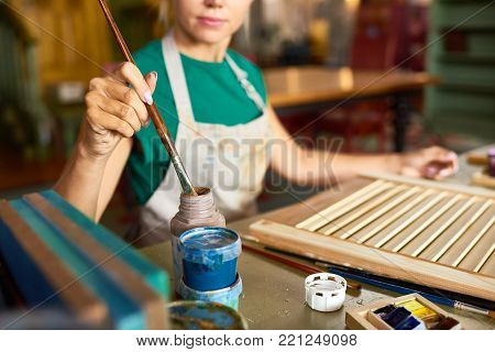 Mid-section portrait of pretty blonde woman enjoying work in art studio painting picture frame with paint, focus on female hand dipping brush in paint