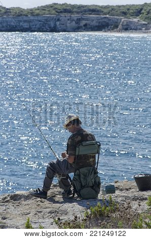 Torre dell'Orso, Italy - September 22, 2017: Solitary old fisherman on the Salento cliff