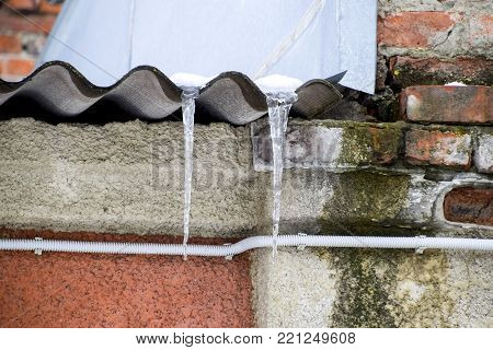 Icicles on the roof. Insecure roof. Freezing water in the icicle