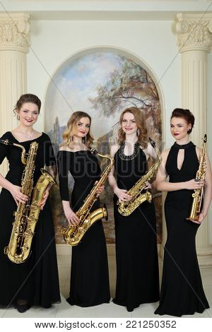 MOSCOW - APR 30, 2017: Four women (with model releases) stands with saxophones in studio Cross photo