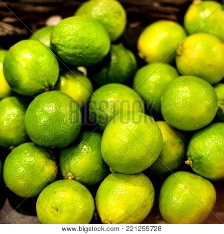 Organic pile of green Limes on  a local farmer market. Healthy local food market concept  in vintage hipster style.
