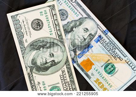 The old and new version design of one hundred US dollar notes on a black background