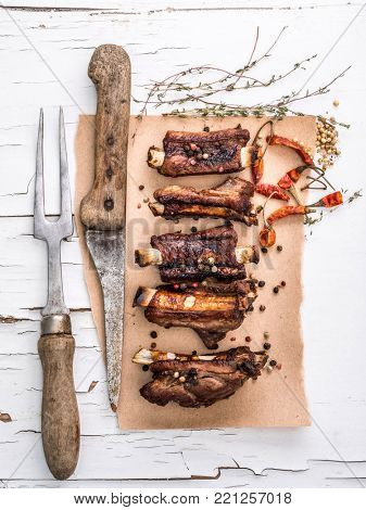 Delisious homemade pork ribs on a piece of brown pape with carving fork and spices, top view