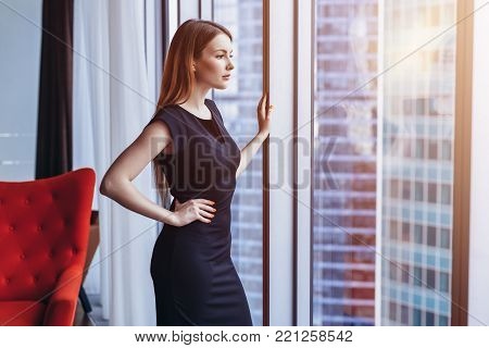 Well-off attractive woman thinking standing at the window admiring cityscape in her penthouse apartment.