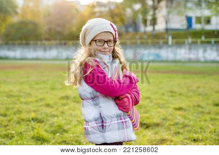 Outdoor portrait of adorable aucasian girl 7 years old, with blond long curly hair, in glasses and a knitted cap.