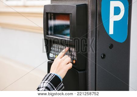 A modern terminal for paying for car parking. The person presses the buttons and pays for the parking. Modern technology in everyday life