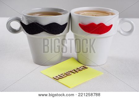 Mutual relations of a male-female. Restart. Symbolic cups of a man-woman and the text restart with wooden letters.