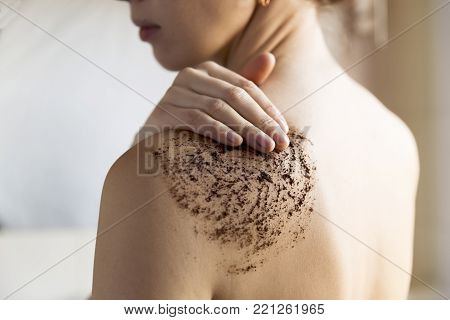 Beauty, spa and healthy skin concept - woman cleans skin of the body with coffee scrub in bathroom.