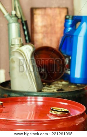 Car servicing  oil change. Red oil barrel canister in mechanic garage auto service or shop. Industry detail.