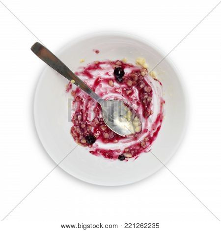 Food leftovers after breakfast for recycling. An overhead photo of dirty spoon and a bowl with porridge and bilberry jam leftovers. Isolated on white. Messthetics aesthetic concept