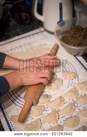 Close up of woman hands holding rolling pin and preparing traditional polish christmas dish called pierogi, dumplings filled with mushroom and onion filling