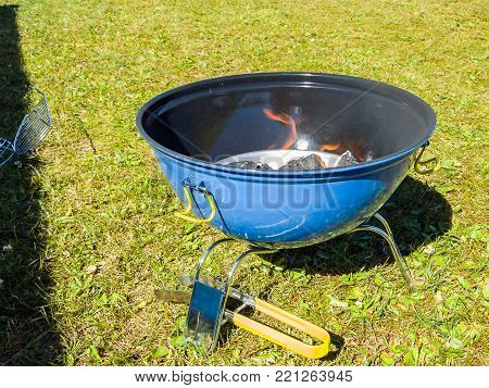 A Blue Barbeque Grill With Charcoal Burning With Flames