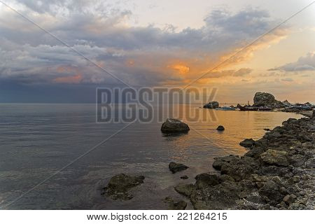 Clouds in the light of the setting sun. The Black Sea coast. The resort town of Sudak, Crimea.