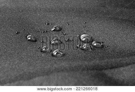 Dark waterproof fabric with waterdrops close up