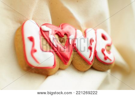 Letter cookies for Valentine's day or for a wedding day on the background of coarse calico fabric. Top view, copy space.
