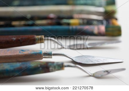 fine art, creativity and artistic tools concept - palette knives or painting spatulas and paintbrushes