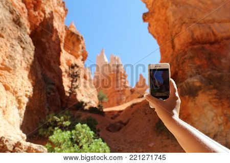 Woman taking smart phone picture of Rock Hoodoos in Bryce Canyon National Park in Utah. USA