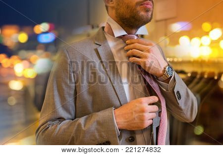 sale, shopping, fashion, style and people concept - close up of young man in suit choosing and tying tie in mall or clothing store