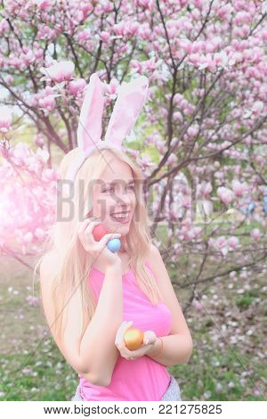girl or adorable woman smiling with colorful eggs in pink, bunny ears on long, blond hair in rosy top in blossoming magnolia garden on floral environment. Spring. Easter, holidays, celebration