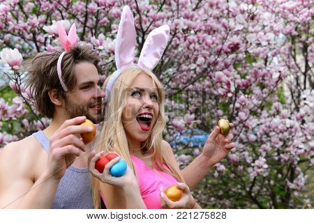 couple in love with bunny ears holding colorful eggs on floral environment. Handsome man, macho or boyfriend and cute girl, pretty woman or girlfriend smiling at blossoming trees. Spring. Easter