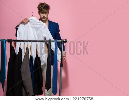 Businessman with tie in blue jacket on bare torso. Man choose necktie on wardrobe rack on green background. Business fashion, style concept. Clothing, dressing, closet. Shopping, sale, purchase