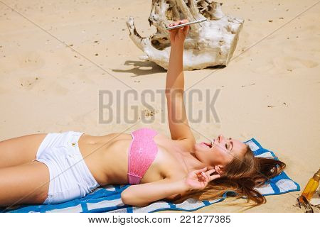Fun and joy. Summer time. Young beauty girl spending time on beach taking selfie photo by mobile phone. Positive woman with smartphone lying on blanket.