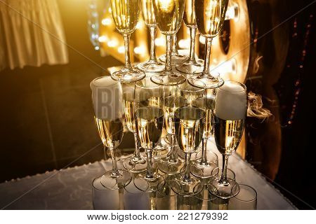 Glasses of champagne made in a pyramid for event party or wedding ceremony. Pyramid of glasses of champagne for celebrate in party with background of light bulbs