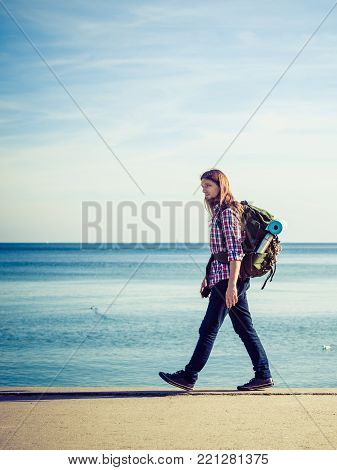 Man hiker backpacker walking with backpack by seaside at sunny day. Adventure, summer, tourism active lifestyle. Young long haired guy tramping poster