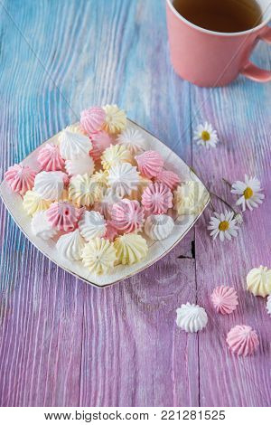 Tasty different marshmallows with chamomile flower on a color gradient background