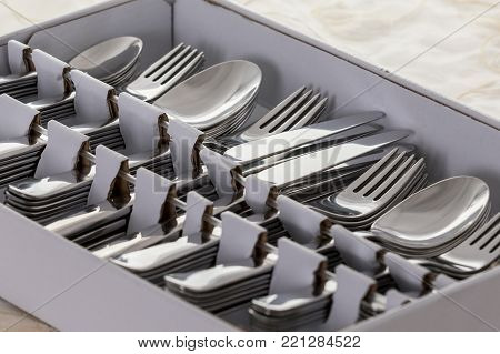New from the store, spoons, forks, knives, cake forks and teaspoons in a box, on table with white tablecloth, twelve of each piece. Close view