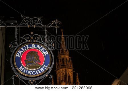 MUNICH, GERMANY - DECEMBER 17, 2017: Paulaner Beer logo in front of Munich New Town Hall (Neues Rathaus) at night. Paulaner Bier is one of the symbols and main beers of Munich and Bavaria