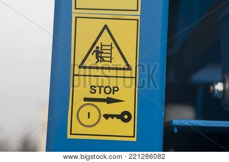 Warning sign on agricultural machinery. Before lifting into the hopper with the grain stop the car, turn off the ignition and take out the key.