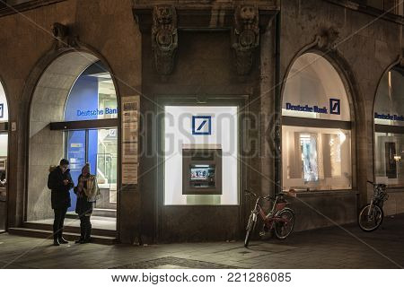 MUNICH, GERMANY - DECEMBER 17, 2017: Deutsche Bank logo and ATM on one of their Munich branches taken during a snowy night. Deutsche Bank is one of the main German global banking and financial services company