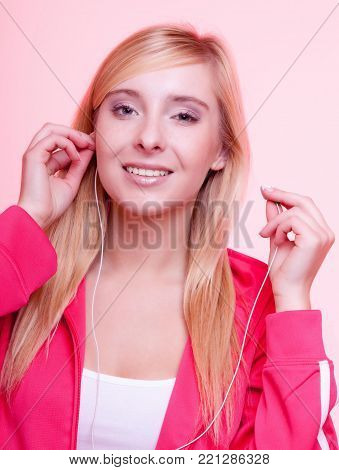 fitness lifestyle concept - woman doing sports and listening to music. Teen girl with headphones use mp3 music player relax gym on pink background