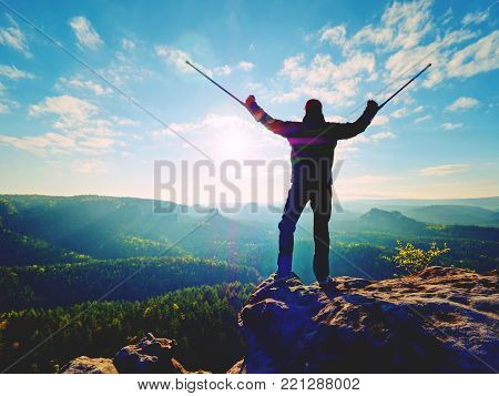 Disabled man with forearm crutches on the edge. View over the hilly ladscape in summer evening. Hurt leg on bandage with crutches