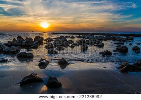 Large stones on a sandy beach in tidal waves. Bright sunset on the coast of the Mediterranean Sea in Caesarea. Warm winter in Israel. Concept of ecological tourism