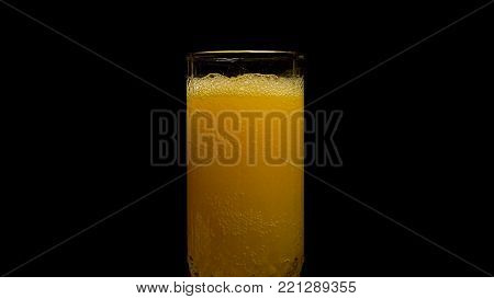Orange soda large glass, overflowing glass of orange soda closeup with bubbles isolated on black background. Pouring Orange Drink. Slow Motion. Carbonated orange drink is poured into a glass. Pouring orange juice soda in glass in slow motion,