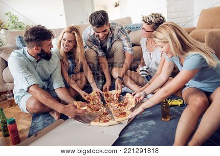 Leisure,food and drinks,people and holidays concept-smiling friends eating pizza and drinking beer.