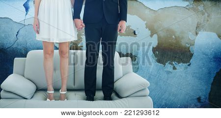Low section of couple standing on sofa  against rusty weathered wall