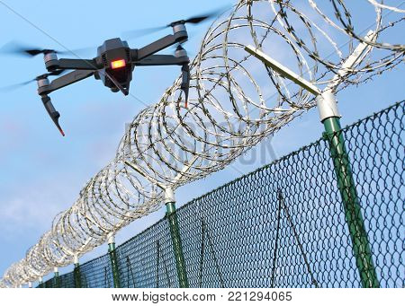 Drone monitoring barbed wire fence on state border or restricted area. Modern technology for security.
