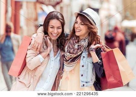 Shopping and tourism concept-beautiful girls with shopping bags in city.