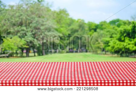 Empty table with red tablecloth over blur garden and bokeh background, for food and product display montage